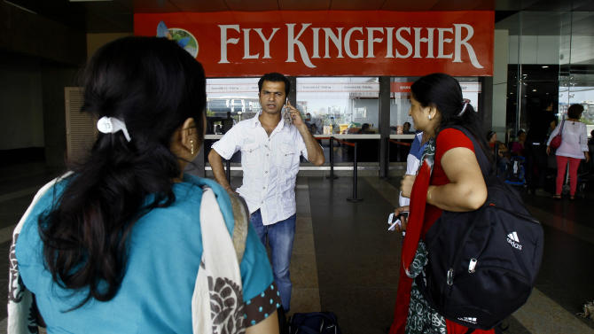 Passengers wait outside the Kingfisher Airlines reservation counter after their flight was canceled at the domestic airport in Mumbai, India, Monday, Oct 1, 2012 Kingfisher says it has canceled several flights Monday due to a labor dispute with its workforce, local media reported. (AP Photo/Rafiq Maqbool)