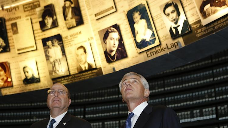 U.S. Defense Secretary Chuck Hagel, right, stands next to Israel's Defense Minister Moshe Yaalon as he looks at pictures of Jews killed in the Holocaust during a visit to the Hall of Names at Yad Vashem's Holocaust History Museum in Jerusalem on Sunday, April 21, 2013. (AP Photo/Baz Ratner, pool)