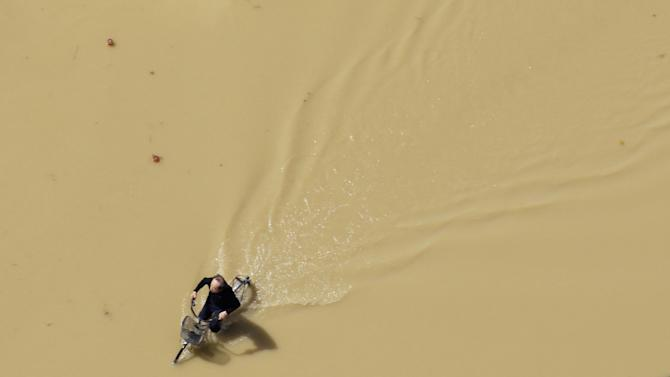 FILE - In this Sept. 11, 2015 file photo, a man rides a bicycle in a road flooded with murky water in Joso, Ibaraki prefecture, northeast of Tokyo. Two days of torrential rain caused flooding and landslides across much of Japan this week. (Masanori Takei/Kyodo News via AP, File) JAPAN OUT, CREDIT MANDATORY