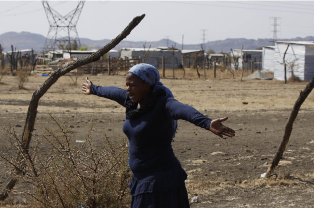 A woman from a group of churchgoers  wails at the site, Sunday Aug. 19, 2012 at the Lonmin platinum mine near Rustenburg, South Africa, during a memorial service for 34 dead striking miners who were s