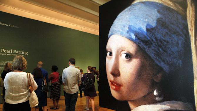 "This June 19, 2013 photo shows visitors entering the ""Girl with a Pearl Earring: Dutch Paintings from the Mauritshuis"" exhibit during a media preview at the High Museum of Art in Atlanta. The exhibit, which opens Sunday and runs through Sept. 29, includes Johannes Vermeer's famous ""Girl With a Pearl Earring"" painting and 34 other works from the Dutch Golden Age. (AP Photo/Jaime Henry-White)"