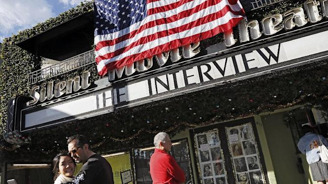 "Bernard Denney takes a selfie with his girlfriend Maho Tanaka, left, in front of the Cinefamily at Silent Movie Theater in Los Angeles on Thursday, Dec. 25, 2014 prior to attending the movie ""The Interview."" The film's Christmas Day release was canceled by Sony after threats of violence by hackers linked to North Korea, but the release was reinstated in some independent theaters and through a variety of digital platforms. (AP Photo/Richard Vogel)"