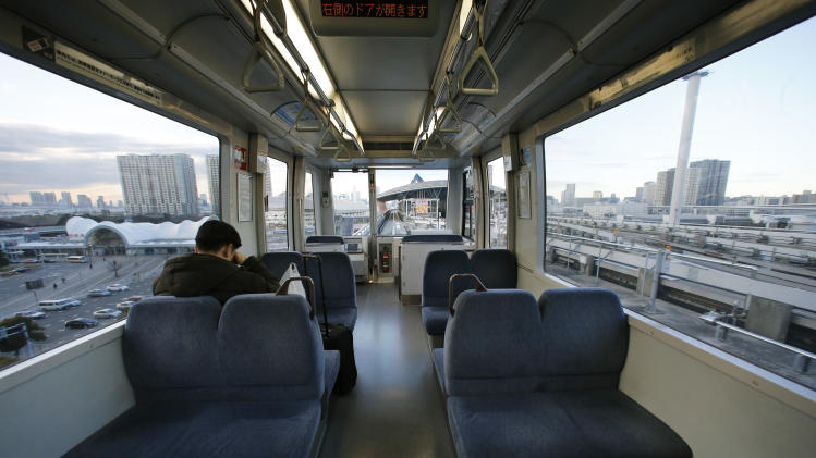 In this Jan. 10, 2013, photo, a man rides a train on Tokyo's Yurikamome Line that runs without any drivers or conductors along Tokyo Bay. Katsuya Hagane, the manager in charge of operations at New Transit Yurikamome, which employees just 60 regular employees, says the automated systems  reduce the number of staff needed. (AP Photo/Shizuo Kambayashi)