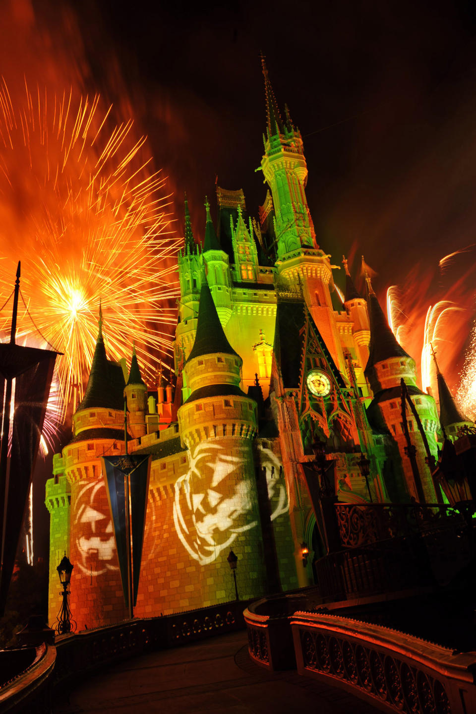 "This undated image released by Disney shows orange fireworks exploding over Cinderella's Castle while illuminated pumpkins are projected with light during the ""Happy HalloWishes"" fireworks show at Magic Kingdom in Lake Buena Vista, Fla. (AP Photo/Disney, Gene Duncan)"