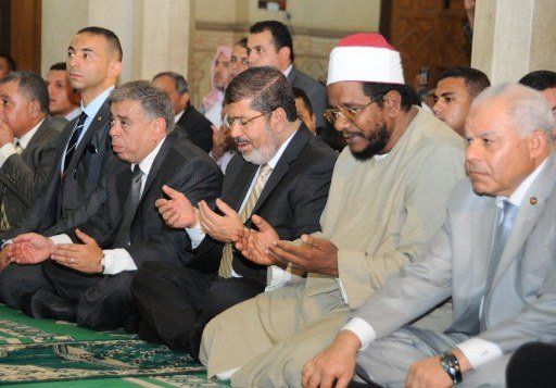 A handout photograph released by the Egyptian Presidency, shows Egyptian President Mohamed Morsi (3R) performing Friday noon prayers at a mosque in the district of Fayoum, south west of Cairo, during
