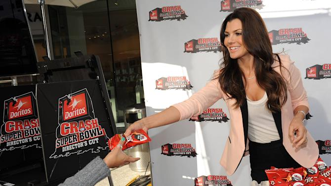 """IMAGE DISTRIBUTED FOR DORITOS - In this image released on Monday Jan. 7, 2013, Iconic """"Doritos Girl"""" Ali Landry celebrates the 15th anniversary of her first Doritos Super Bowl spot """"Laundromat"""" by casting her vote in this year's Doritos Crash the Super Bowl program in Los Angeles. (Photo by Jordan Strauss/Invision for Doritos/AP Images)"""