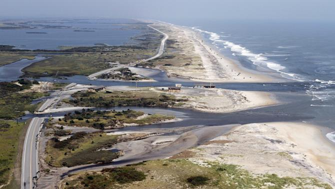 Officials survey the damage to route 12 on Hatteras Island, NC., Sunday, Aug. 28, 2011.  Hurricane Irene swept through the area Saturday cutting the roadway in five locations.  Irene caused more than 4.5 million homes and businesses along the East Coast to reportedly lose power over the weekend, and at least 11 deaths were blamed on the storm.   (AP Photo/Steve Helber)