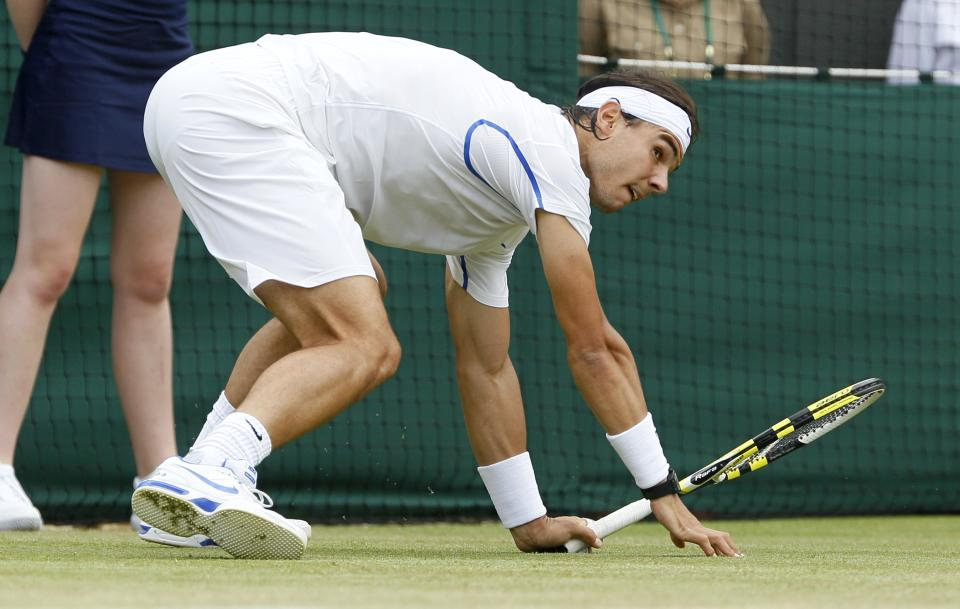 Spain's Rafael Nadal falls to the ground during his match against Luxembourg's Gilles Muller at the All England Lawn Tennis Championships at Wimbledon, Saturday, June 25, 2011. (AP Photo/Alastair Grant)