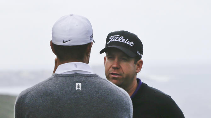 Erik Compton, right, a two-time heart transplant recipient, talks with Tiger Woods during a delay on the third tee  at Torrey Pines during the third round of the Farmers Insurance Open golf tournament Sunday, Jan. 27, 2013, in San Diego. (AP Photo/Lenny Ignelzi)