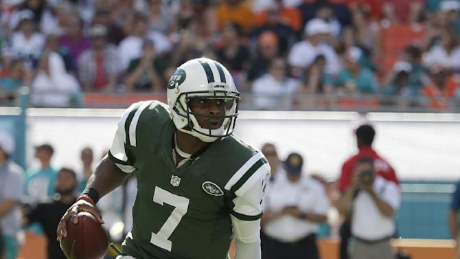 New York Jets quarterback Geno Smith (7) avoids a tackle by Miami Dolphins defensive tackle Randy Starks (94) during the first half of an NFL football game, Sunday, Dec. 28, 2014, in Miami Gardens, Fla. (AP Photo/Lynne Sladky)