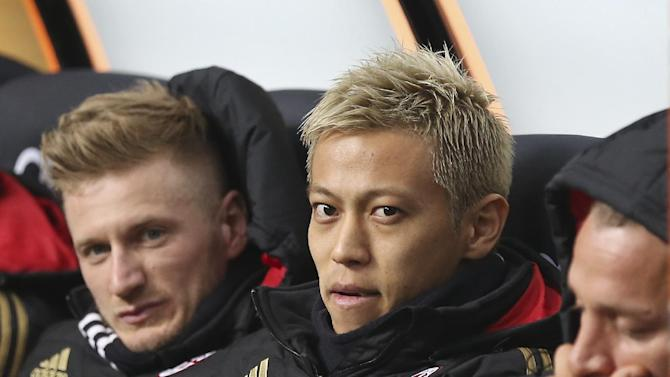 AC Milan forward Keisuke Honda, center, of Japan, sits on the bench by his teammates Ignazio Abate, left, and Philippe Mexes, of France, prior to the start of the Italian Cup soccer match between AC Milan and Udinese at the San Siro stadium in Milan, Italy, Wednesday, Jan. 22, 2014
