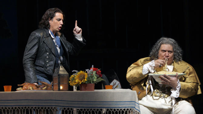 "In this Sept. 20, 2012 photo, Ambrogio Maestri, right, performs as Dulcamara alongside Matthew Polenzani performing as Nemorino during the final dress rehearsal of Gaetano Donizetti's ""L'Elisir d'Amore"" at the Metropolitan Opera in New York. That most endearing of all comedies, Donizetti's ""L'Elisir d'Amore,"" opened the Metropolitan Opera season on Monday, Sept. 24 in a modest new production made memorable by an outstanding cast. (AP Photo/Mary Altaffer)"