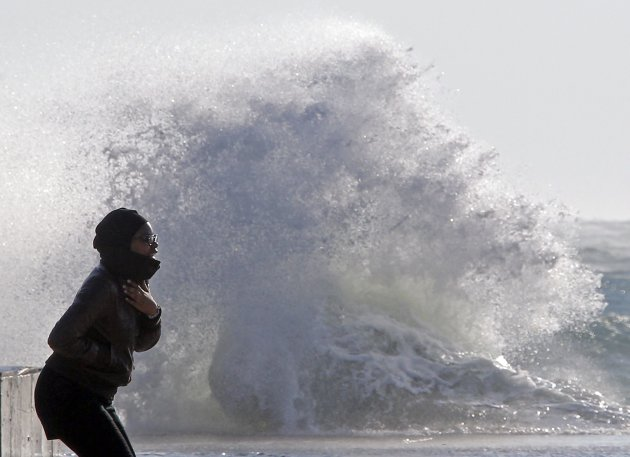 A woman watches a wave hitting the waterfront in Marseille
