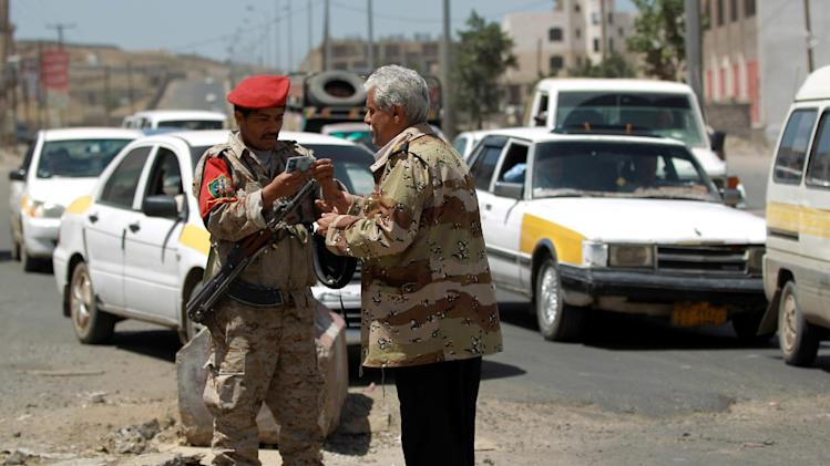 A Yemeni soldier checks the identity of a man at a checkpoint in the capital Sanaa on April 15, 2014