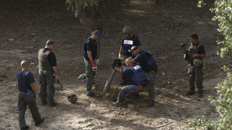 Israeli police sappers remove the remains of an ordnance fired by Palestinian militants from the Gaza Strip that landed in the southern Israeli town of Ashkelon, Monday, Nov. 19, 2012. Exchange of fire between Israel and Gaza militants continued for the sixth day on Monday.(AP Photo/Tsafrir Abayov)