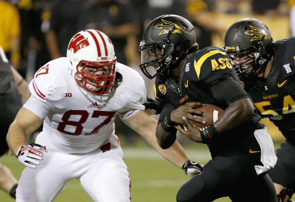 Arizona State's Marion Grice, right, carries the ball as he tries to get past Wisconsin's Ethan Hemer (87) in the first half of an NCAA college football game on Saturday, Sept. 14, 2013, in Phoenix. (AP Photo/Ross D. Franklin)