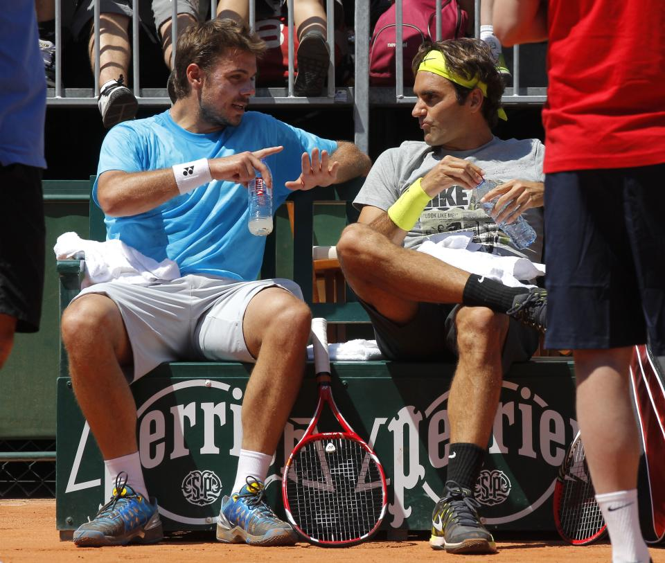 Switzerland's Roger Federer, right, listens to compatriot Stanislas Wawrinka   as they train for the French Open tennis tournament at the Roland Garros stadium in Paris, Saturday, May, 26, 2012.  (AP Photo/Michel Euler)