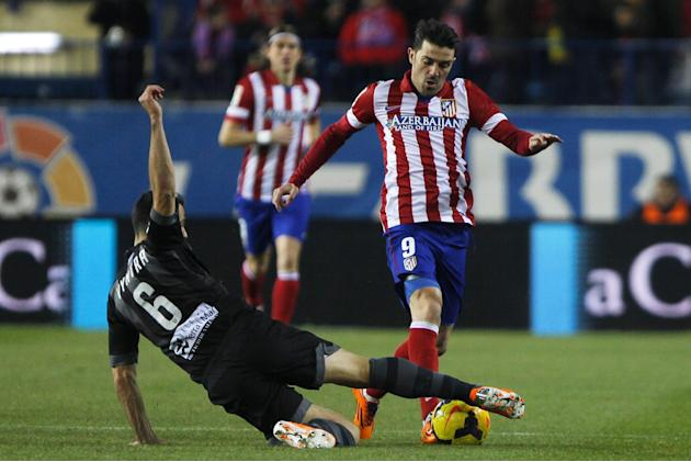 Atletico's David Villa, right, competes with Loukas Vyntra from Greece, left, during a Spanish La Liga soccer match between Atletico de Madrid and Levante at the Vicente Calderon stadium in Madrid