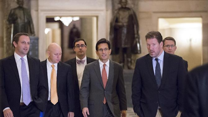 House Majority Leader Eric Cantor, R-Va., center, walks to the floor of the House for the final series of votes on a bill to fund the government, in Washington, Saturday, Sept. 28, 2013. Locked in a deepening struggle with President Barack Obama, the Republican-controlled House approved legislation early Sunday imposing a one-year delay in key parts of the nation's health care law and repealing a tax on medical devices as the price for avoiding a partial government shutdown in a few days' time. (AP Photo/J. Scott Applewhite)