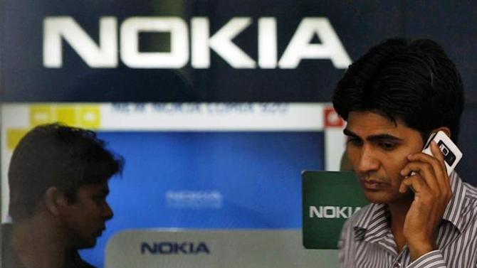 A customer speaks on his mobile phone as he comes out of a Nokia showroom in New Delhi March 28, 2013. REUTERS/Mansi Thapliyal/Files