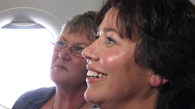 Lynley Bendall, right, and Ally Wanikau, left, smile after the couple were married on a flight that left from Queenstown, New Zealand Monday, Aug. 19, 2013. A law change allowed same-sex couples to marry in New Zealand for the first time Monday. The couple celebrated the legalization of gay marriage in New Zealand by getting hitched in a plane at 39,000 feet (11,900 meters). Bendall and Wanikau celebrated their wedding in the air after they won a promotion by national carrier Air New Zealand. (AP Photo/Nick Perry)