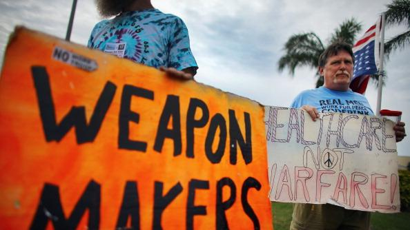 Clay Colson holds a sign reading, ' Healthcare not Warfare!', as he joins others in a protest in front of a Raytheon company building which they say is building military drones on August 23, 2012 in Largo, Florida. The protest is one of many planned by activists who want to state their views on the economy or other issues before and during the Republican National Convention in Tampa, Florida during the week of August 27th. (Photo by Joe Raedle/Getty Images)