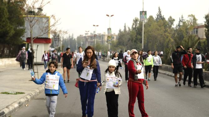 People attend a charity run organized by BASMA to raise funds for the treatment of children with cancer in Syria, at Dummar, west of Damascus