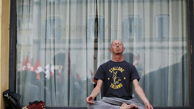 """A protester wearing a t-shirt reading """"Italian stallion"""" meditates as he sits cross-legged and barefooted on a window sill as other demonstrators are reflected in the window during a protest against the government's education reform, in Rome"""