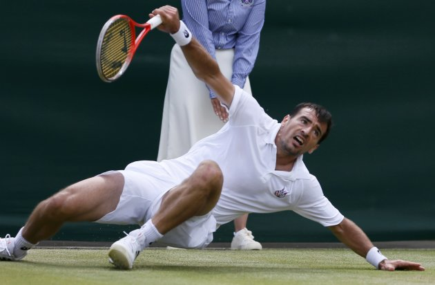 Ivan Dodig of Croatia slips during his men's singles tennis match against David Ferrer of Spain at the Wimbledon Tennis Championships, in London