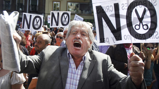 "A man holds a banner reading ""No cuts"" as he shout slogans against healthcare austerity measures announced by the Spanish government in Madrid, Spain, Saturday, Sept. 1, 2012. Some 300 people have blocked a ring road in Madrid to protest the introduction of spending cuts that will leave more than 150,000 non-registered immigrants without healthcare in Spain. Illegal immigrants who do not contribute taxes to social security are, as of Saturday, to lose national health cards that had entitled them to free treatment in case of illness. (AP Photo/Andres Kudacki)"