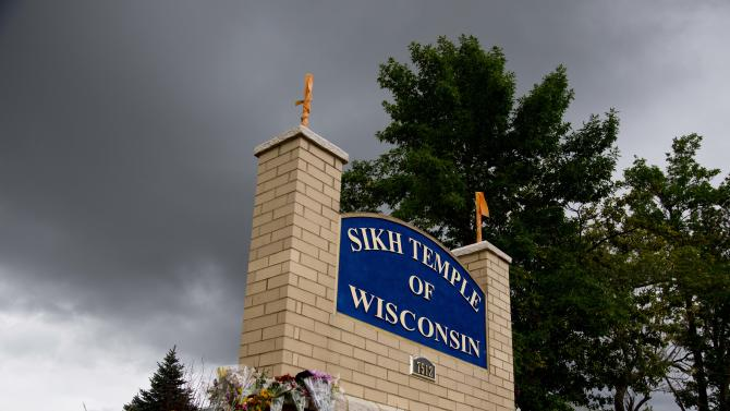 Flowers lie on the sign to the Sikh temple of Wisconsin where members were allowed to re-enter for the first time in Oak Creek, Wis., Thursday, Aug 9, 2012.  The mass shooting last Sunday claimed six members of the temple. (AP Photo/Jeffrey Phelps)