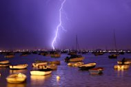 POOLE, ENGLAND - JULY 21: Lightning strikes over Poole Harbour during a thunderstorm on July 21, 2013 in Poole, England. The spell of hot weather was brought to an end last night on the South coast after a second week of heatwave conditions across the UK. (Photo by Dan Kitwood/Getty Images)