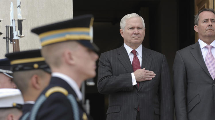 Defense Secretary Robert Gates, left, and British Defense Minister Liam Fox, stand at attention during the playing of the National Anthem at an honor cordon ceremony at the Pentagon, Tuesday, April 26, 2011. (AP Photo/Susan Walsh)