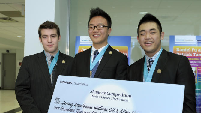 George W. Hewlett High School in Hewlett, N.Y. students, from left, Jeremy Appelbaum, William Gil and Allen Shin pose with their scholarship check at George Washington University in Washington, Tuesday, Dec. 4, 2012,  after being named the top winners of the Siemens Competition in Math, Science & Technology National Finals.  (AP Photo/Susan Walsh)