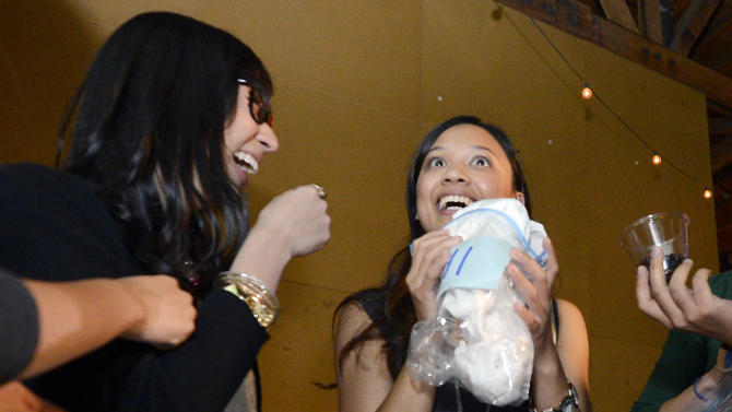Jessica Nguyen, right, reacts after smelling a shirt as Angela Abad-Santos looks on during a pheromone party, Friday, June 15, 2012, in Los Angeles. The get-togethers, which have been held in New York and Los Angeles and are planned for other cities, require guests to submit a slept-in T-shirt that will be sniffed by other participants. Then you can pick your partner based on scent. (AP Photo/Mark J. Terrill)
