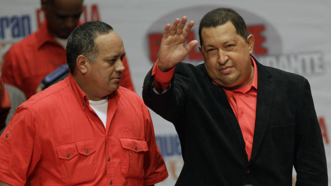 Venezuela's President Hugo Chavez, right, waves to supporters next to  National Congress' President Diosdado Cabello, left, as he attends a concert in his honor atTeresa Carreno theater  in Caracas, Venezuela, Thursday, Feb. 23, 2012. Chavez is headed to Cuba for surgery to remove a potentially cancerous tumor while the nation's congress on Thursday unanimously approved permission for Chavez to leave, a formality required by the nation's constitution. (AP Photo/Fernando Llano)