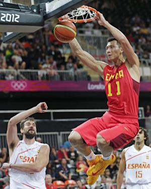 China's Yi Jianlian slams a dunk after getting past Spain's Marc Gasol, left, and Victor Sada, right, during a men's basketball game at the 2012 Summer Olympics, Sunday, July 29, 2012, in London. (AP Photo/Charles Krupa)