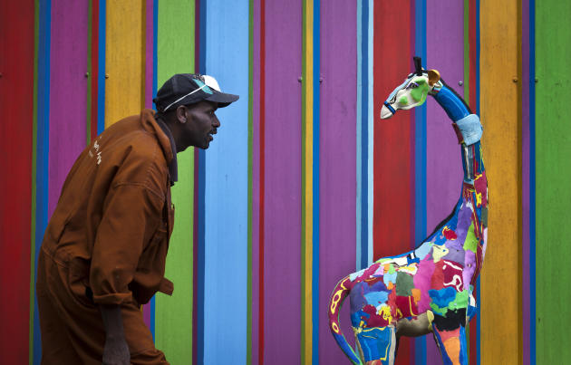 In this photo taken Monday, April 29, 2013, carver Jackson Mbatha, 40, poses next to a an unfinished large toy giraffe he is making from pieces of discarded flip-flops, in front of a painted workshop