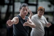 An elderly man and a woman practice Tai Chi in Hong Kong on August 30, 2012