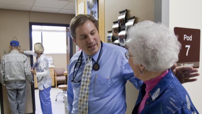 FILE - In this Oct. 26, 2009 file photo, primary care physician Dr. Don Klitgaard greets Muriel Bacon as her husband weighs in with a nurse, at the Myrtue Medical Center in Harlan, Iowa. Unless Congress acts before Jan. 1 doctors will again face steep Medicare cuts that threaten to undermine health care for millions of seniors and disabled people. It's become a symbol of sorts for the federal government's budget dysfunction. (AP Photo/Nati Harnik, File)
