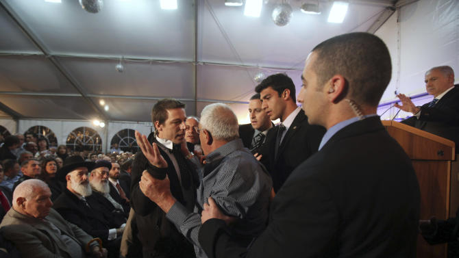 Israeli Prime Minister Benjamin Netanyahu, right, gestures, as security officers gather around Danny Rosen, center, life-partner of Haifa police chief Ahuva Tomer who was killed in last month's massive Carmel forest fire, after he interrupted the official ceremony for the fire victims, in Kibbutz Beit Oren, northern Israel, Wednesday, Jan. 5, 2011. Angry relatives forced Netanyahu to stop his speech at a ceremony honoring 42 Israelis killed in a huge forest fire last month. Family members shouted that he was responsible for the disaster. Others directed their anger at Interior Minister Eli Yishai, who was escorted out of the hall. (AP Photo/Oded Balilty, Pool)