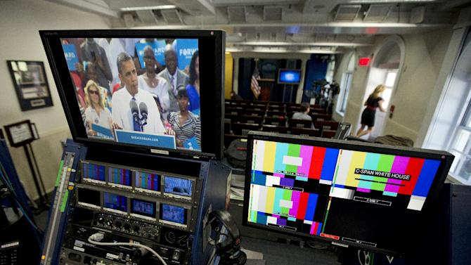 An image of President Barack Obama appears on a television monitor via live feed in an almost empty White House Brady press briefing room in Washington, as the president campaigns in nearby Woodbridge, Va., Friday, Sept. 21, 2012.  The presidential race is in high gear and the president spends much of time on the road pitching for votes in battleground states. The White House press corps that normally occupies space in the West Wing is out there with him, or off covering Republican candidate Mitt Romney. (AP Photo/Manuel Balce Ceneta)