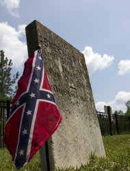 "A Confederate flag graces a soldiers grave stone in Cemetary One at the Confederate Memorial Park in Mountain Creek, Ala., Tuesday, July 19, 2011. More than 60,000 Confederate veterans came home to Alabama after the Civil War, and residents are still paying a tax that supported them 150 years after the fighting began. The tax now pays for the park, which is located on the same 102-acre tract where elderly veterans used to stroll. The tax once brought in millions for Confederate pensions, but lawmakers sliced up the levy and sent money elsewhere as the men and their wives died. No one has seriously challenged the continued use of the money for a memorial to the ""Lost Cause,"" although a long-serving black legislator wants to eliminate state funding for the park. (AP Photo/Dave Martin)"