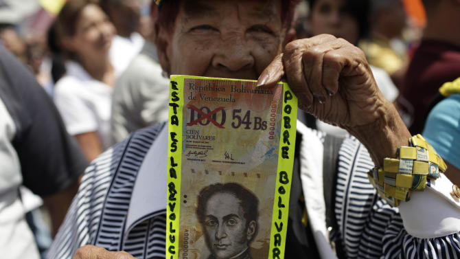 "FILE - In this Feb. 23, 2013 file photo, a protester holds up a fake bill that reads in Spanish ""This is the revolution. Poor Bolivar"" with the value of 100 crossed out and 54 written next to it, at an opposition demonstration against of the devaluation of the currency in Caracas, Venezuela. Thousands of companies suffer under currency controls that all but deny them the U.S. dollars they need to import vital items into this oil-rich country, from food to cars to spare parts, even gasoline. Venezuelan firms must sell their wares at state-controlled prices that don't reflect the 22 percent inflation rate, the highest in Latin America. Even Venezuela's socialist government admits the controls don't work, but its attention is focused on the April 14, 2013 election to replace the late President Hugo Chavez. (AP Photo/Ariana Cubillos, File)"