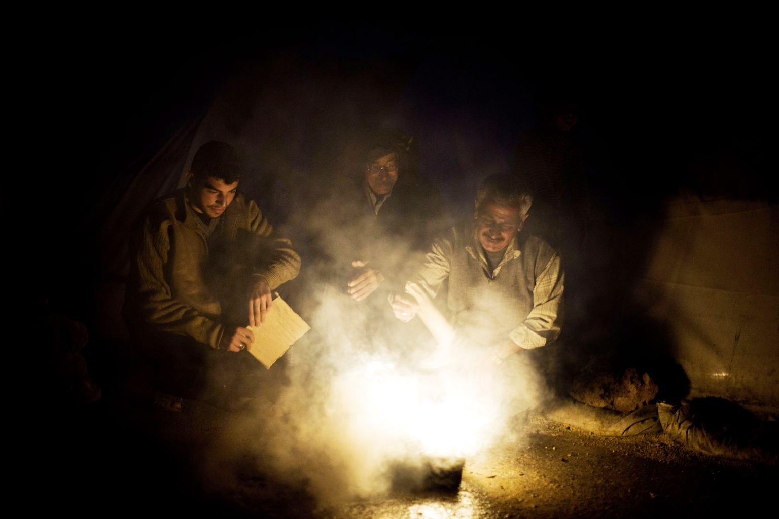 Syrian men heat a fire to boil water near their tent at a refugee camp near the Turkish border, in Azaz, Syria, Sunday, Dec. 9, 2012.
