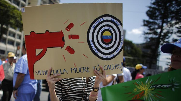 Anti-government doctor holds a placard during a march to demand medical supplies for hospitals in Caracas