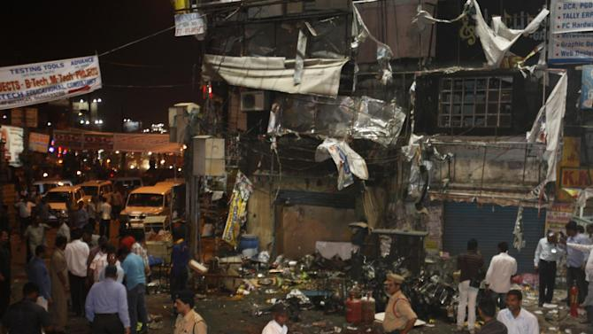 People and police officers stand at the spot after a bomb blast in Hyderabad, India, Thursday, Feb. 21, 2013. A pair of bombs exploded Thursday evening in a crowded shopping area in the southern Indian city of Hyderabad, killing several people and wounding many in the worst bombing in the country in more than a year, officials said. (AP Photo/Mahesh Kumar A.)