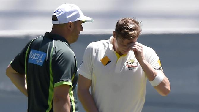 Australia's team trainer Alex Kountouris, left, assists captain Steve Smith after an injury during play on day two of their cricket test match against India in Melbourne, Australia, Saturday, Dec. 27, 2014. (AP Photo/Andy Brownbill)