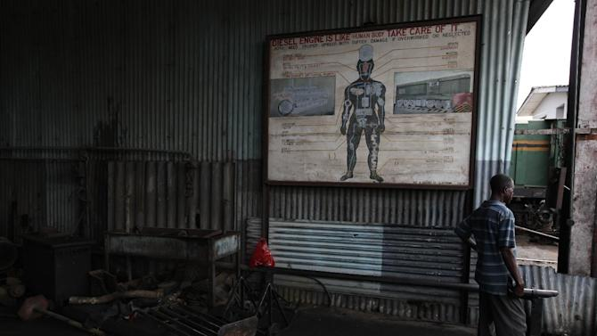 An engineer stands near a sign comparing the human body to a train engine in Lagos, Nigeria, on Saturday, April 14, 2013. The Nigerian Railway Corp., while recently restarting service from Lagos to the northern city of Kano, still has relics from the past littering the grounds of its headquarters in Lagos. Historians hope to preserve some of these old locomotives and train cars for future generations to see. (AP Photo/Jon Gambrell)
