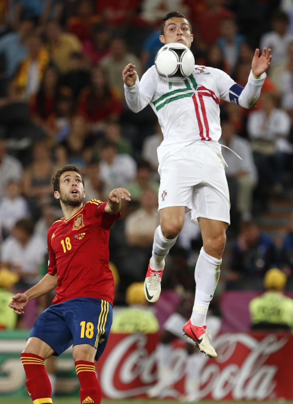 Portugal's Cristiano Ronaldo outleaps Spain's Jordi Alba for a ball during the Euro 2012 soccer championship semifinal match between Spain and Portugal in Donetsk, Ukraine, Wednesday, June 27, 2012. (AP Photo/Armando Franca)